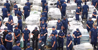 Coast Guard Cutter Stratton crew members amidst packages of cocaine seized in recent USCG busts. Photo: USCG via YouTube.
