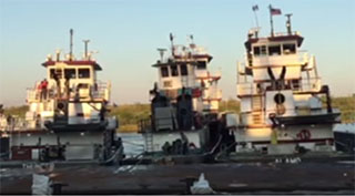 Towboats prepare to flip a barge. Screenshot via YouTube - Jeremy McLain.