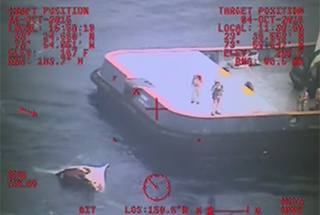 Coast Guard divers prepare to enter the water to investigate a damaged life boat from El Faro. USCG image.