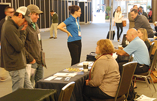 Job seekers talk to representatives of marine employers at the 2015 International WorkBoat Show job fair. Kirk Moore photo.