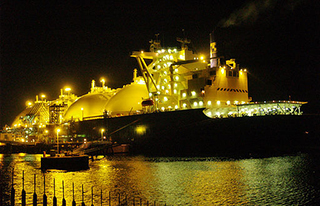 An LNG carrier at night. Wikimedia Commons photo by Tam Tam.
