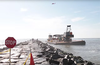 Crews work to refloat a grounded barge. NJ.com video screenshot.