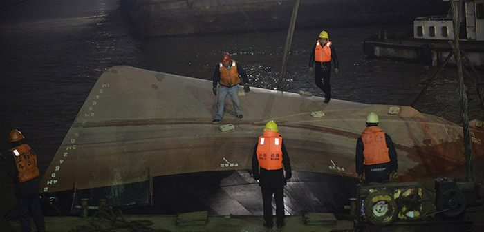 Responders stand on the hull of the capsized tugboat Wan Shenzhou 67. Xinhua News Agency photo.