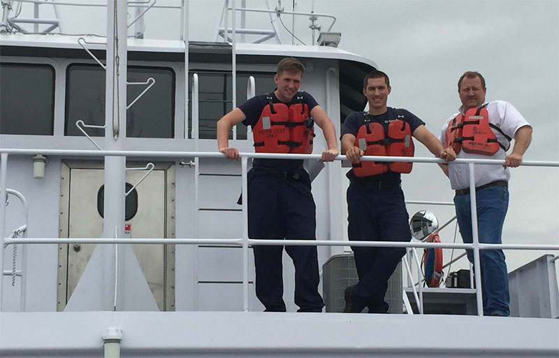 Coast Guard cadets Ben Morseth and Mason Totri (center) stand with John Belcher, captain of Canal Barge Company's Lainey Jones in 2015. Canal Barge Company photo.