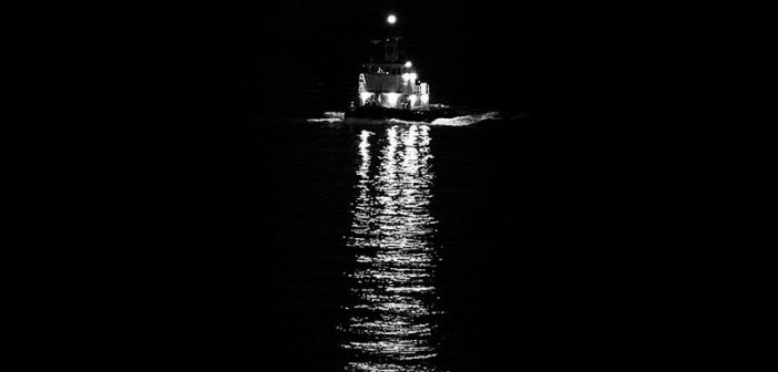 Lights from a tug underway at night. Creative Commons photo by Guian Bolisay.