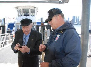 Imperatore and senior deckhand George Schumpp check ferry schedule timing on a smartphone. Kirk Moore photo.