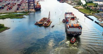 A containership passes a dredge in the Arthur Kill channel between Staten Island and New Jersey. Corps of Engineers photo