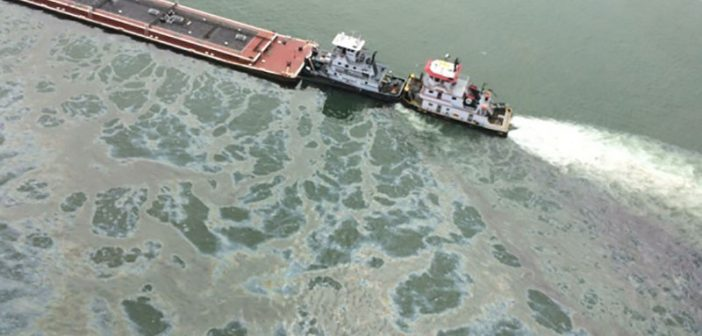 A barge loaded with marine fuel oil sits partially submerged in the Houston Ship Channel after the March 22, 2014 collision with bulk carrier Summer Wind. USCG photo.