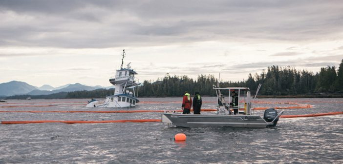 Containment boom surrounds the partially submerged Kirby tug Nathan E Stewart, which ran aground in British Columbia on Oct. 13. Canadian Coast Guard photo.