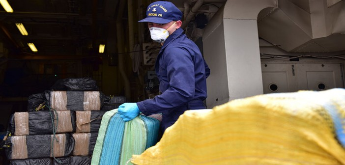 A crewmember from Coast Guard Cutter Waesche offloads cocaine from an earlier seizure in June 2016.