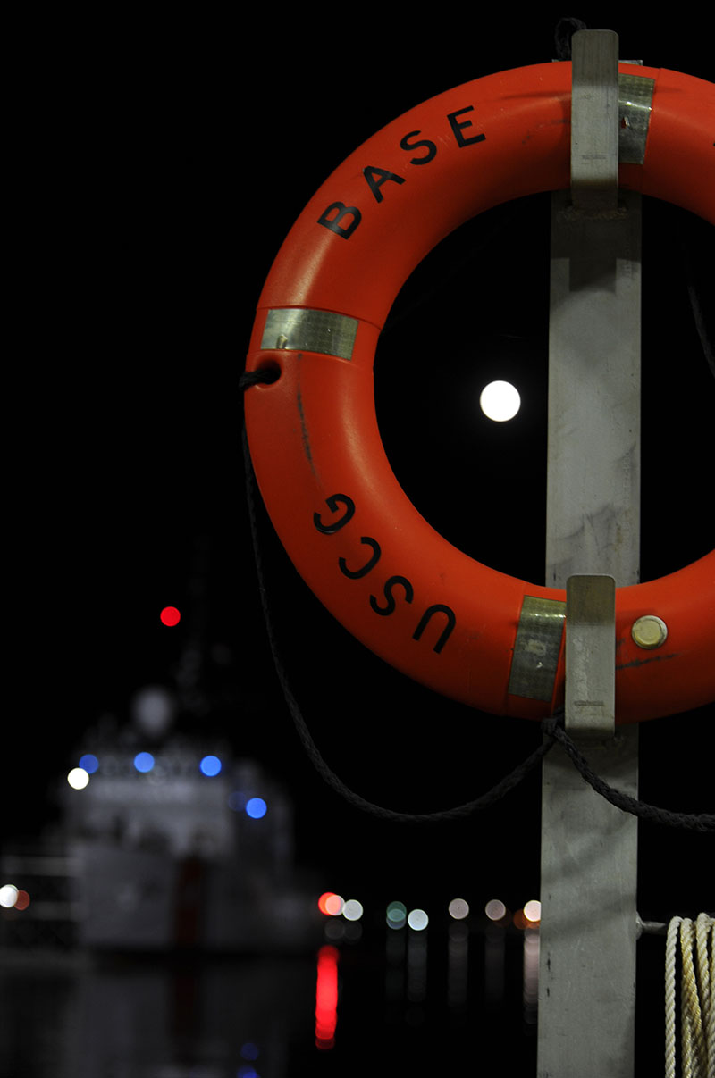 The moon is visible through a mounted ring buoy as it shines over Coast Guard cutter Legare at Coast Guard Base Portsmouth, Nov. 13, 2016. U.S. Coast Guard Photo by Coast Guard Petty Officer 3rd Class Corinne Zilnicki.