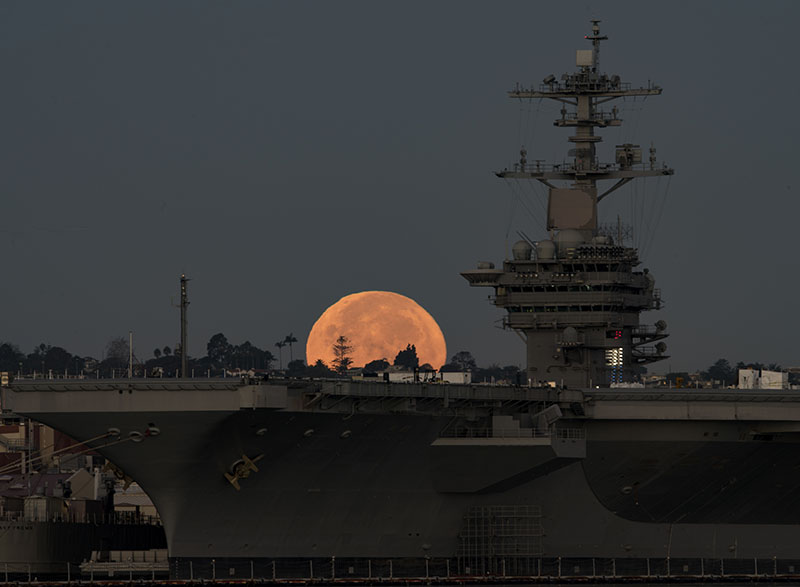 The brightest moon in almost 69 years sets behind the aircraft carrier USS Theodore Roosevelt, moored and homeported in San Diego. U.S. Navy photo by Petty Officer 2nd Class Abe McNatt.