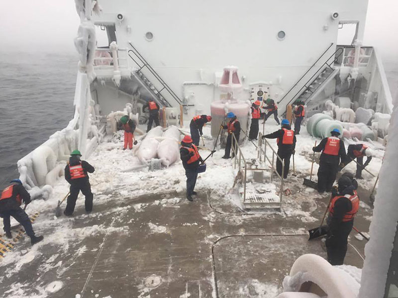 The crew of the Coast Guard Cutter Alder clears ice from the deck of the cutter as the ship transits through Lake Superior Dec. 14, 2016. USCG photo.