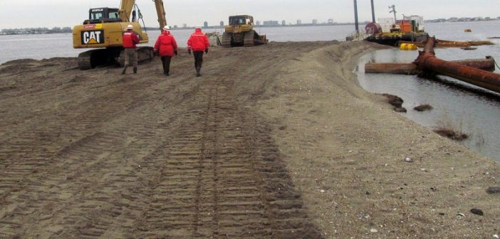 Corps of Engineers personnel walk on freshly recreated portion of Yellow Bar Hassock Marsh Island made from sand pumped from a nearby dredge at an ecosystem restoration project in Jamaica Bay in Queens, N.Y.