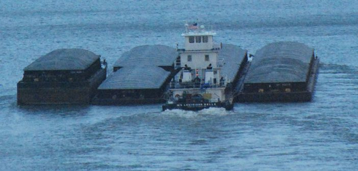 A towboat and hopper barges move down the Mississippi River. Kirk Moore photo.