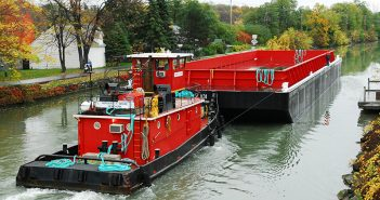 The tug, Herbert P. Brake, of New York, pushes a new barge east on the Erie Canal in Fairport, NY in October 2007. Creative Commons photo by Bill Blevins.