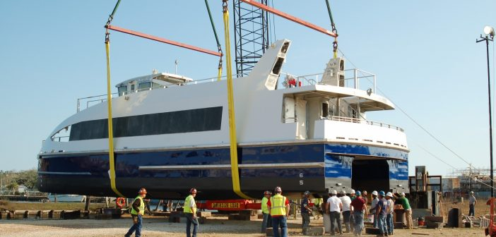 The first of 13 Citywide Ferry Service ferries being built in Alabama moves by crane from a crawler to the water. Ken Hocke photo.