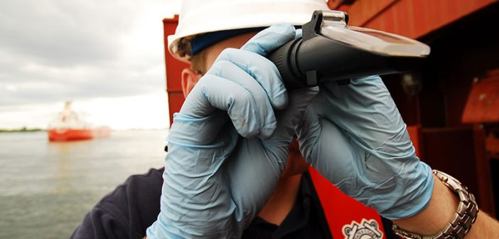 A USCG inspector peers through a refractometer at a sample of ballast water. USCG photo.