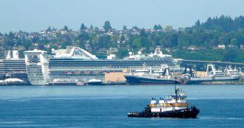 A tug passes before docked cruise ships on Puget Sound's Elliott Bay. Creative Commons photo by Chuck Taylor.