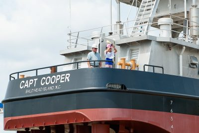 Talyn Corbin swings the champagne bottle to christen the Capt Cooper as Metal Trades chairman Rusty Corbin watches. Metal Trades photo.