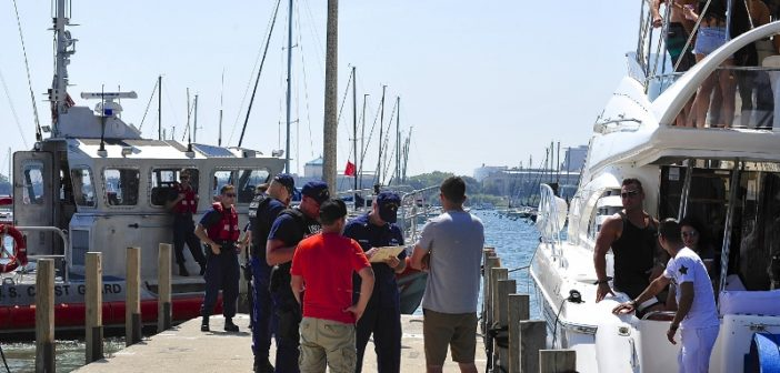 A Coast Guard crew verifes proper documentation and interview a boat operator and deckhand during a safety inspection at Monroe Harbor in Chicago, Aug. 19, 2017. Coast Guard photo/MCPO Alan Haraf