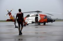 A Coast Guard rescue swimmer, carrying an ax and chainsaw for urban rescues, walks to board a helicopter. Coast Guard photo.