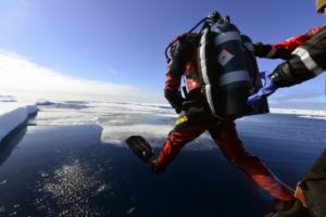 Coast Guard Petty Officer 1st Class Brendon Ballard enters the water from a Coast Guard cutter Healy small boat during a cold water ice dive in the Arctic, July 30, 2017. U.S. Coast Guard photo/PO2 Meredith Manning.