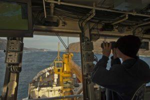 Coast Guard Cutter Maple crew member Seaman Jeffery Moore keeps lookout from the bridge as the Maple follows Canadian Icebreaker Terry Fox into Bellot Strait in Nunavut, Canada, August 12, 2017. U.S. Coast Guard/PO2 Nate Littlejohn.
