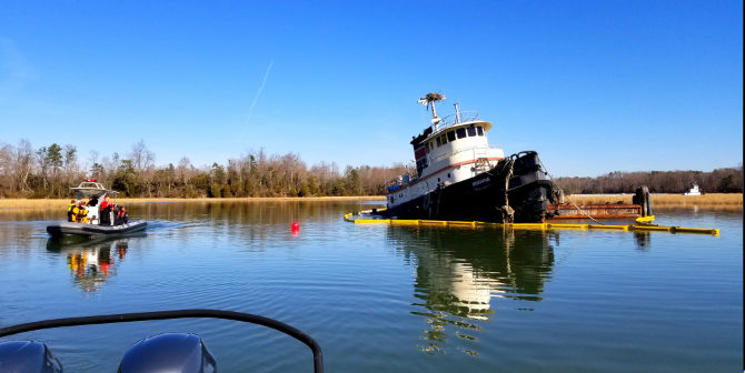 A Coast Guard pollution response team from Coast Guard Sector Hampton Roads surveys the area around partially submerged tugboat Bourne on Skiffes Creek, Virginia, Jan. 22, 2018. Coast Guard photo.