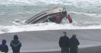 Two Coast Guardsmen from Station Chetco River work to rescue a man from the cabin of an overturned U.S. Army Corps of Engineers survey vessel resting on the beach in Brookings, Ore., April 25, 2018. Coast Guard photo.
