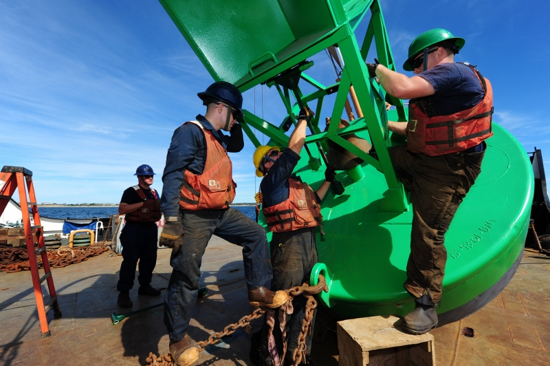 Members of Coast Guard cutter Willow's buoy deck crew work together to install the clappers on a bell buoy before the buoy is set in the water near Block Island, R.I. Coast Guard photo/PO3 MyeongHi Clegg.