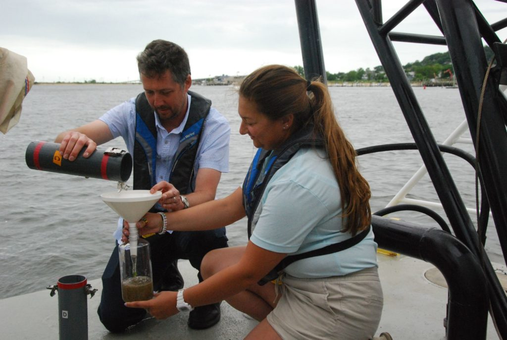 Monmouth University professor Jason Adolf and senior Taylor Donovan decant a bottle from a sample trawl. Kirk Moore photo.