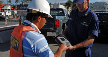 Petty Officer 1st Class Robert Fairchild, with the U.S. Coast Guard Incident Management Division, checks a port security guard's Transportation Worker Identification Credential  (TWIC) at Young Brothers in Honolulu. U.S. Coast Guard photo/PA3 Luke Clayton