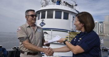 Capt. Megan Dean, commander of Coast Guard Sector Miami, issues a certificate of inspection to Capt. Steven Johnson, captain of the Kirby tugboat Miami at the Port of Miami, July 20, 2018. Coast Guard photo/PO3 Brandon Murray.