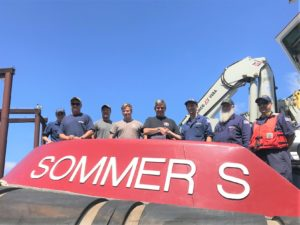 Coast Guard marine inspectors Lt. Mary Morgan, Petty Officer 1st Class Jeff Deronde, Mike Pearson and Chief Petty Officer David Labadie all from Marine Safety Unit Portland, present a Subchapter M Certificate of Compliance to the crew of the towing vessel Sommer S., operated by Shaver Transportation, in Portland, Ore., July 20, 2018. Coast Guard photo/ Lt. Anthony Solares.