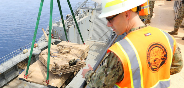 A Navy officer supervises as a 60-ton M1 Abrams tank is lowered during a delivery at Aquaba, Jordan, in 2014. Marine Corps photo/MSgt. Will Price.
