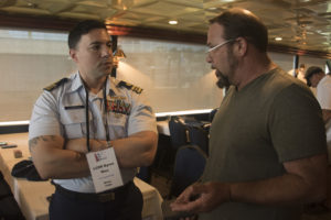 Coast Guard Lt. Cmdr. Byron Rios, a prevention officer at Coast Guard 7th District Miami, speaks with Tim Harris, a passenger vessel owner, in Clearwater, Florida, Sept. 19, 2018. Coast Guard photo/PO2 Ashley J. Johnson.