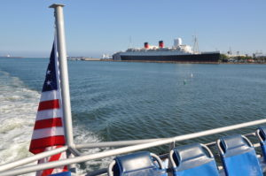 The Jet Cat Express cruises by the Queen Mary in Long Beach Harbor. Photo by David Krapf
