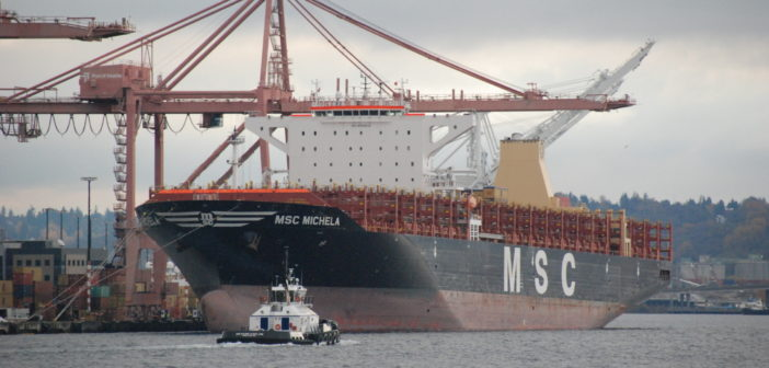 The Harley Marine Services tug Dr. Hank Kaplan passes a containership at the Port of Seattle. Kirk Moore photo.