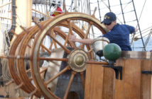 Seaman Preston Cox, a helmsman on the Coast Guard training ship Eagle, maintains the ship's heading by steering a compass course in May 2010. Coast Guard photo/PO2 Jetta H. Disco.