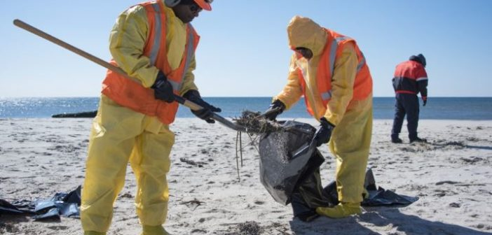 Workers from Miller Environmental Group Inc. clean oil residue from the beach at Jacob Riis Park Beach in New York on April 1, 2019. Tar balls were reported on the beach after a containership was discovered leaking fuel at a Staten Island terminal. Coast Guard photo/PO3 Ryan Dickinson