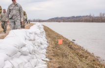 U.S. Airmen assigned to the 139th Airlift Wing, Missouri Air National Guard, pick up trash along a levee, after laying a half-mile of sandbags for addition reinforcement along the Missouri River, in Elwood, Kan., on March 23, 2019. (U.S. Air National Guard photo by Tech. Sgt. Patrick Evenson)