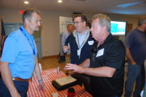New Jersey charter and party boat captain Eddie Yates, right, and Ocean County senior planner Steven Simone talk to Jens Grangaard at a public outreach meeting hosted by wind developer Ørsted in Waretown, N.J. Kirk Moore photo