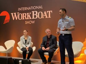 Cmdr. Carlos Crespo of the Coast Guard's Office of Boat Forces, right, talks about small boat acquisition with Mark Porvaznik and Jen Sokolower at the International WorkBoat Show. Kirk Moore photo.