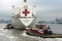 The hospital ship Comfort entered New York Harbor with a flotilla of tugs, Coast Guard and police escorts March 30, 2020. David Rider photo..